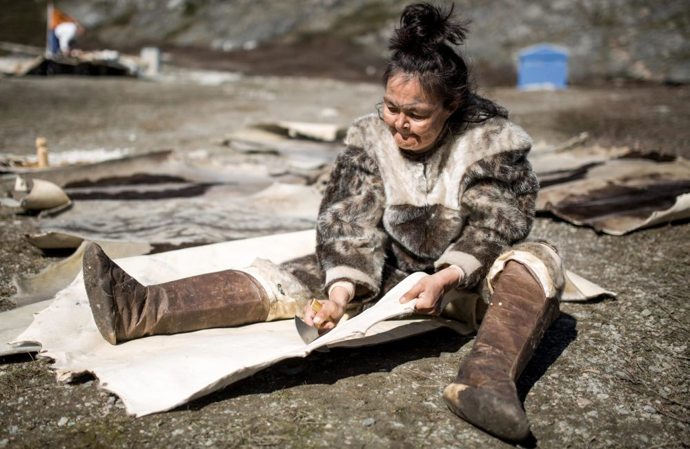 A woman carving seal skin for a tent at the living village museum in Qasigiannguit in Greenland-min